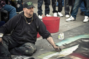Chalkmaster Dave sitting on sidewalk drawing