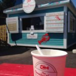 Cup of chowder with food shack in background