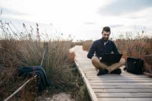 Man seated with laptop on boardwalk