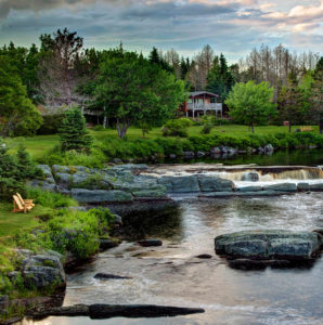 Adirondack chairs by babbling brook with cottage