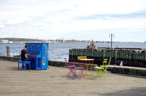 Person playing piano by the waterfront