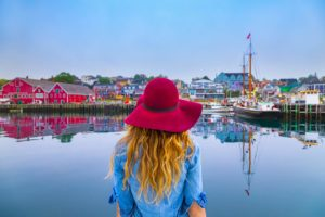 Woman wearing hat watching out at waterfront