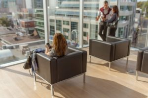 Woman seated in chair looking at mobile phone facing toward windows of office building