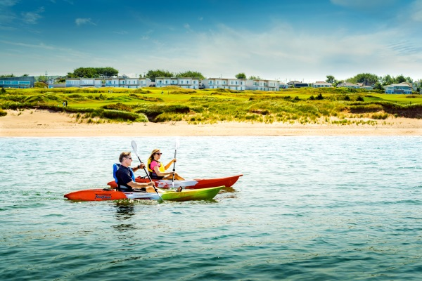 Two kayakers paddling in front of Cabot Links